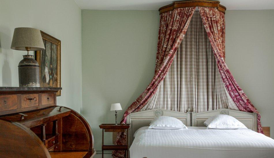 Chambre avec lit baldaquin et mobilier